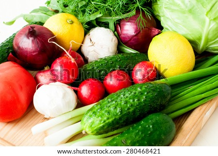set of fresh vegetables for the salad - young cabbage, green onions, red onions, dill and parsley, lemon and garlic on a white wooden background - stock photo