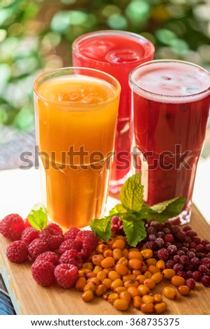 set of fruit non-alcoholic drink with cranberries raspberries and sea buckthorn - stock photo
