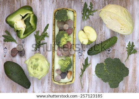 Set of fruits and vegetables on white painted wooden background: kohlrabi, cucumber, apple, pepper, cabbage, broccoli, avocado, rucola. - stock photo