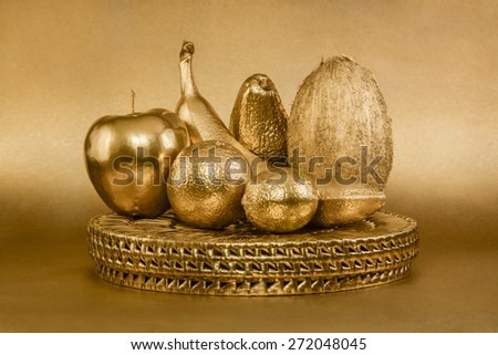 Set of fruits with golden peel on gold background - stock photo