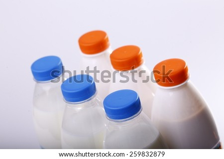 set of full bottles with milk with blue and orange colour lid - stock photo