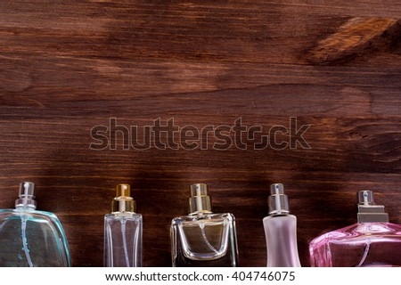 Set of glass bottles Perfume for women of different sizes and colors on a wooden background. Flat Lay