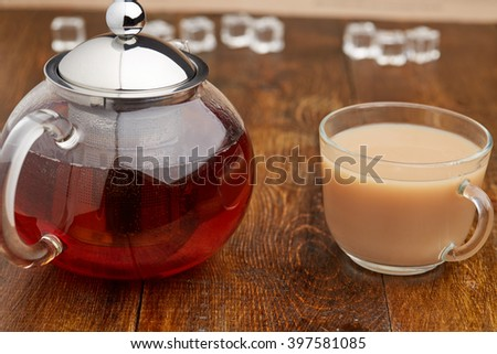 Set of glass teapot and teacup of black tea with milk on wooden table - stock photo