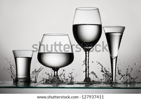Set of glasses for alcoholic drinks with water splash - stock photo