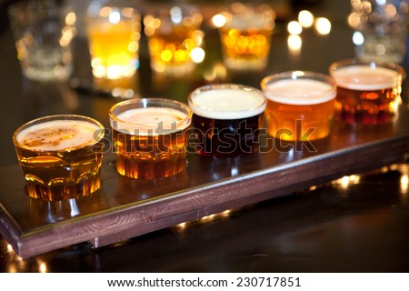 Set of glasses of light and dark beer on a pub background. - stock photo