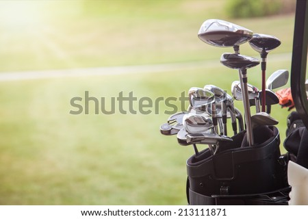 set of golf clubs over green field background