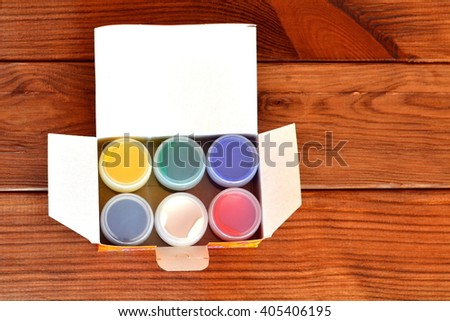 Set of gouache paints on a brown wooden background - stock photo