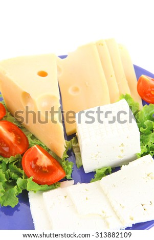 set of gourmet delicatessen cheese slice and chunk ( bar)  white goat greek yellow french aged on green lettuce salad with tomatoes on blue plate isolated over white background - stock photo