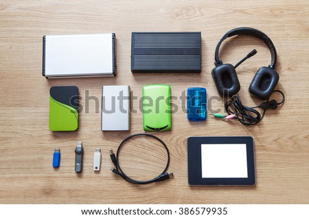 set of hard drives, memory cards, card reader, tablet, phones lying on wooden floor closeup - stock photo