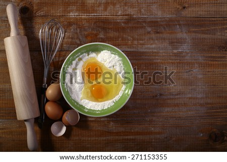 Set of ingredients and appliances for cooking on wooden table top with yolk in flour copyspace, horizontal picture - stock photo
