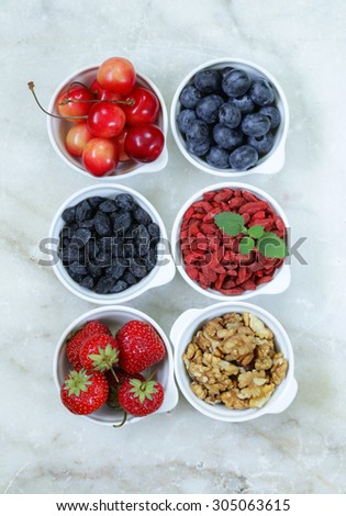 set of ingredients for a healthy food breakfast - muesli, fresh and dried fruit, nuts, goji berries - stock photo