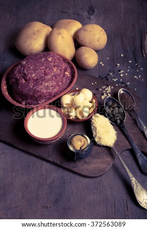Set of ingredients for cooking on old wooden background. Toned.