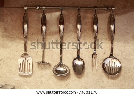 set of kitchen utensils hanging on the wall - stock photo