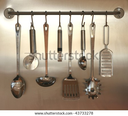set of kitchen utensils hanging on wall - stock photo