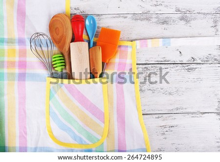 Set of kitchen utensils in pocket of apron on wooden background - stock photo