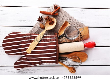 Set of kitchen utensils with cinnamon sticks and star anise in mitten on wooden background - stock photo
