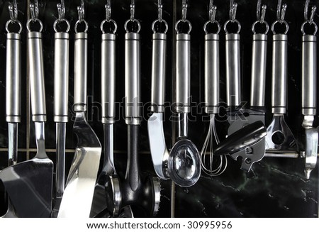 Set of kitchenware hanging on the dark tiled wall - stock photo