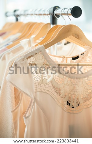 Set of light colored dresses on a wooden hangers - stock photo