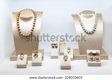 Set of luxury jewelry with precious gems and diamonds. Necklaces made of natural pearls on a stands. Women accessories - stock photo