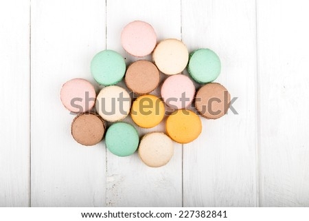 Set of macarons isolated on white wooden table - stock photo