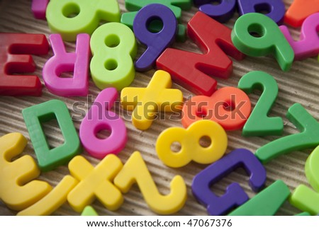Set of magnetic letters and digits on a paperboard background