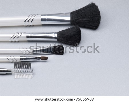 set of make-up brushes on a grey background
