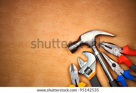 Set of manual tools over a wood panel with space for text - stock photo