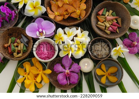 Set of many frangipani ,soap ,salt and orchid in bowl on green leaf - stock photo
