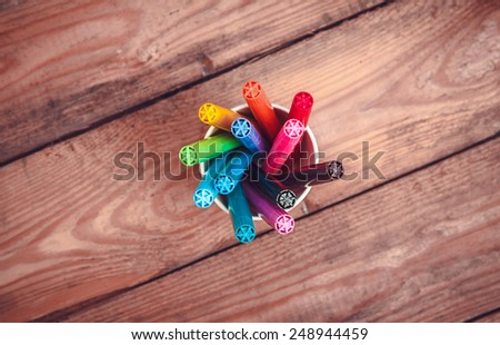 Set of markers in a paper cup on old wooden table. top view - stock photo