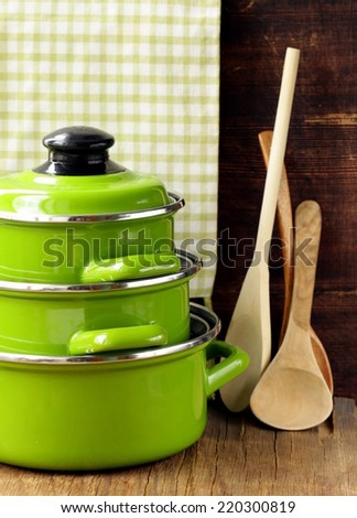 set of metal green pots cookware on a wooden background - stock photo
