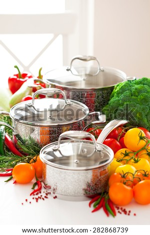 Set of metal pots cookware and fresh vegetables, selective focus - stock photo