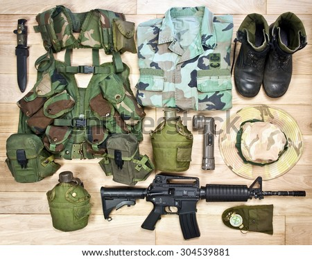 set of military equipment of the Vietnam War era on the wooden background - stock photo