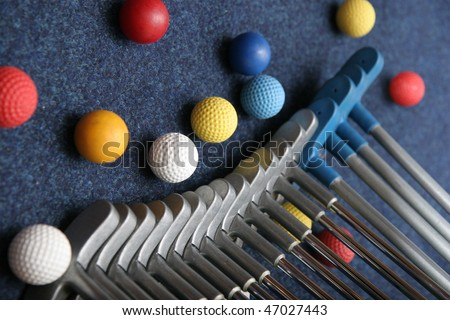 Set of mini golf clubs and color balls on blue covering - stock photo