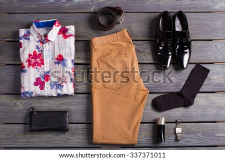 Set of modern men's clothing on a dark wooden background. - stock photo