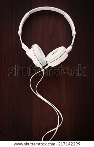 Set of modern white stereo headphones for listening to music on a storage device such as an MP3 player, on black - stock photo