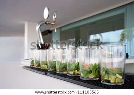 Set of mojitos forming a line over a bar table. - stock photo