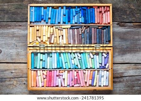 Set of multicolored pastel crayons in open wooden artist box on rustic wooden desk, top view. - stock photo