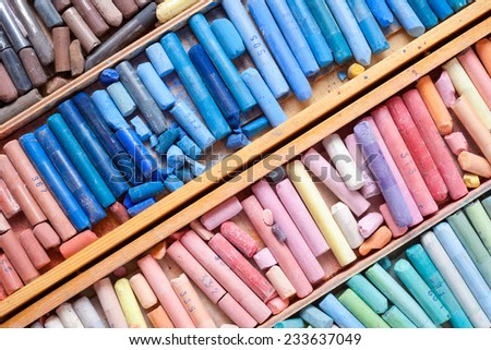 Set of multicolored pastel crayons in wooden artist box closeup, top view - stock photo