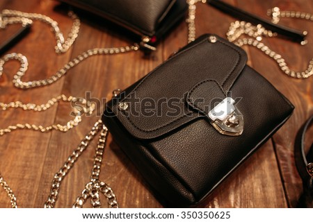 Set of new stylish women's leather handbags.Top view. Several different bags on the wooden background - stock photo