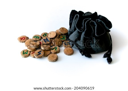 Set of oak runes, an ancient alphabet known as the futhark on white with draw string pouch.  - stock photo