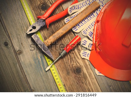 set of old tools to work, measuring tape, gloves and orange construction helmet on a vintage textured boards. instagram image filter retro style - stock photo