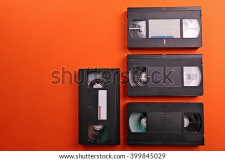Set of old video cassettes on red background