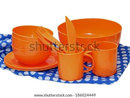 Set of orange plastic utensils for picnic on colorful napkin - stock photo