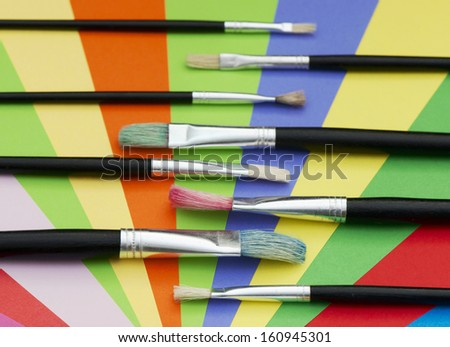 Set of paint brushes and colored paper. - stock photo