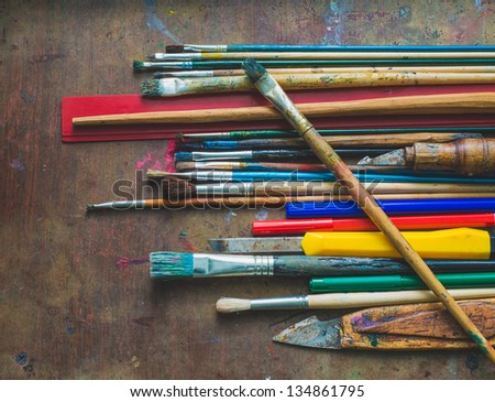 Set of paint brushes and office supplies on the table - stock photo
