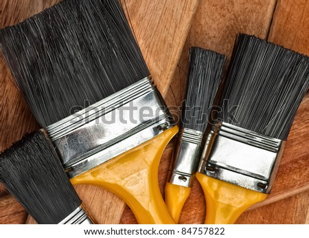 Set of paint brushes on wooden boards - stock photo