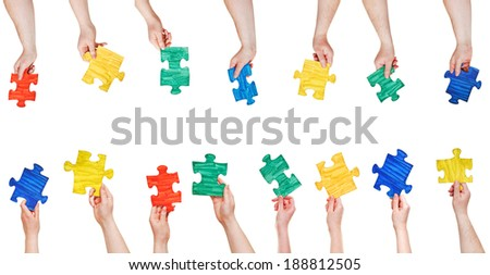 set of painted puzzle pieces in people hands isolated on white background