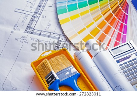 set of painting tools paint brushes in tray rolls blueprints color palette calculator  - stock photo
