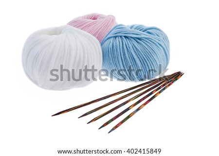 Set of pastel wool yarn wrapped in hanks and a pair of wooden double pointed knitting needles - stock photo