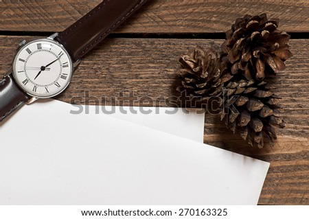 Set of pines watch and paper sheets on wooden table - stock photo